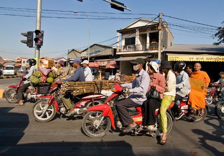 Phnom Penh, Cambodia, December 25, 2007 People on motorcycles waiting at a traffic light. Motorcycle is the main means of motorized transportation for many in Cambodia. Motorcycles are very often overloaded with goods and passengers.
