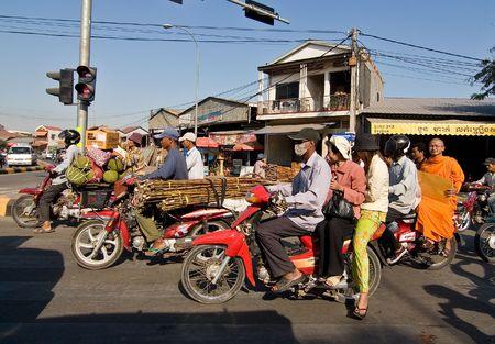 motorizado: Phnom Penh, Camboya, el 25 de diciembre de 2007, personas en motocicletas, esperando en un sem�foro. Motocicleta es el principal medio de transporte motorizado para muchos en Camboya. Motocicletas muy a menudo est�n sobrecargados con mercanc�as y pasajeros.