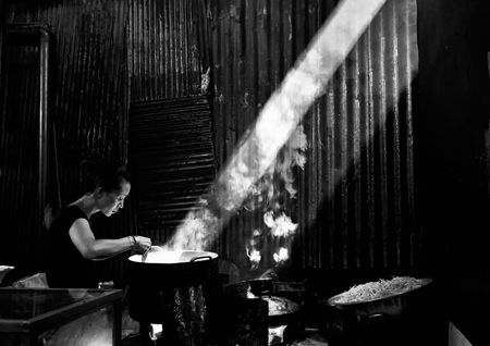 Phnom Penh, Cambodia, December 25, 2007, A black and white photo of a Cambodian woman cooking in a market in Phnom Penh. The ray of light is fortuitously coming through a hole in the roof. Editorial
