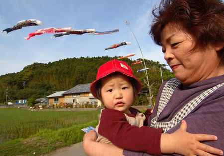 Miyazaki Prefecture, Japan, May 5, 2006, A Japanese grandmother holds her grandson in rural Japan as koi nobori wind socks fly in the background.
