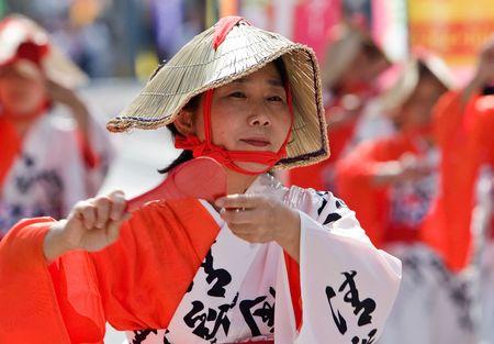 Kagoshima City, Japan, October 28, 2007. A women wearing a straw hat and a white and red yukata  dancing during the Taniyama Furusato Matsuri dance festival. Editorial