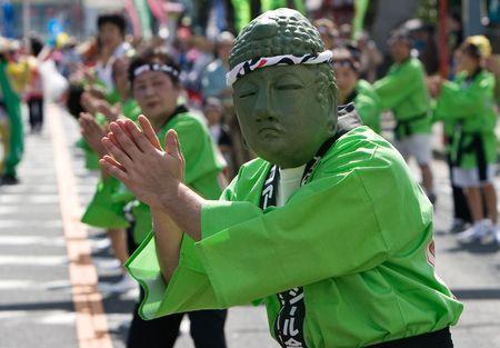 Kagoshima City, Japan, October 28, 2007. A man wearing a buddha mask green hakama jacket leading a group dancing during the Taniyama Furusato Matsuri dance festival.