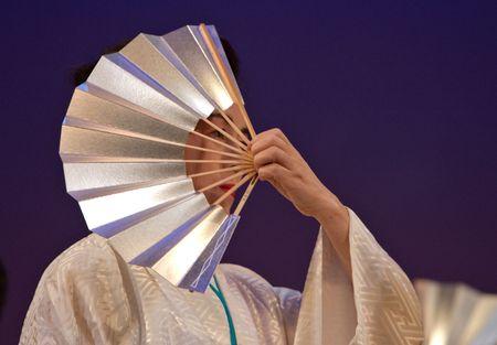 Kagoshima City, Japan, October 27, 2007. An older Japanese dancer in kimono perform with a fan onstage in the Taniyama Furusato Matsuri festival held in Kagoshima City, Japan.