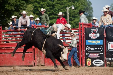 Caledonia, Ontario, Canada, August 16, 2009.  Cowboys look on as a rodeo cowboy rides a bull during the bull riding competition at the Stampede Days Rodeo  in Caledonia, Ontario, Canada.