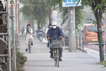 Kagoshima City, Japan, June 3, 2010. Cyclists cover their faces to protect from ash which blanketed the city after an eruption of the volcano Sakurajima.