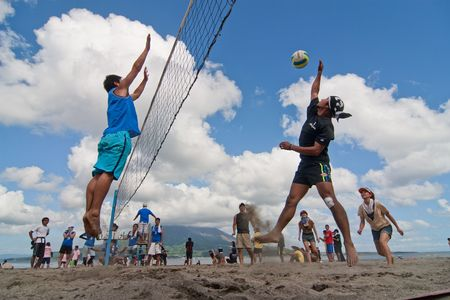 Kagoshima City. A male volleyball player jumps to spike at the Iso Beach beach volleyball competition in Kagoshima City. Active volcano Sakurajima is in the background.