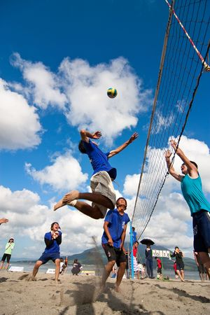 spikes: Kagoshima City, Japan, July 1, 2007. A male volleyball player jumps to spike at the Iso Beach beach volleyball competition in Kagoshima City. Active volcano Sakurajima is in the background.