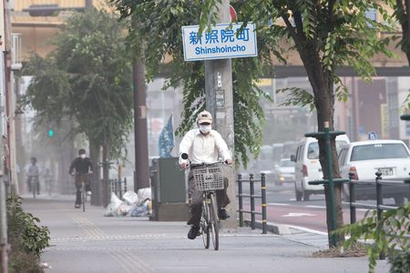 Kagoshima City, Japan, June 3, 2010. Cyclists cover their faces with masks to protect from ash which blanketed the city after an eruption of the volcano Sakurajima.