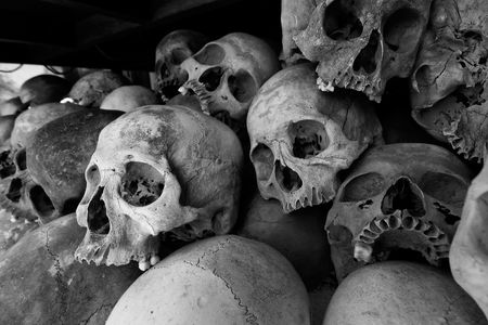 Black and white photo of the skulls of torture victims resting in a stupa at the Killing Fields outside of Phnom Penh, Cambodia.  Stock Photo
