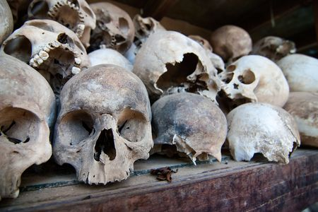 The skulls of torture victims resting in a stupa at the Killing Fields outside of Phnom Penh, Cambodia.  Stock Photo