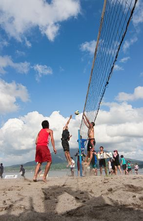 Kagoshima City, Japan, July 1, 2007. A male volleyball player jumps to spike at the Iso Beach beach volleyball competition in Kagoshima City. Active volcano Sakurajima is in the background.