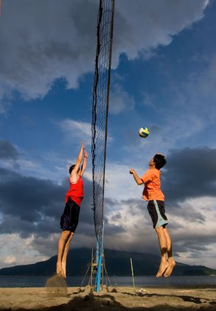 Kagoshima City, Japan, July 1, 2007. A male volleyball player jumps to spike while practicing at the Iso Beach beach volleyball competition in Kagoshima City. Active volcano Sakurajima is in the background.