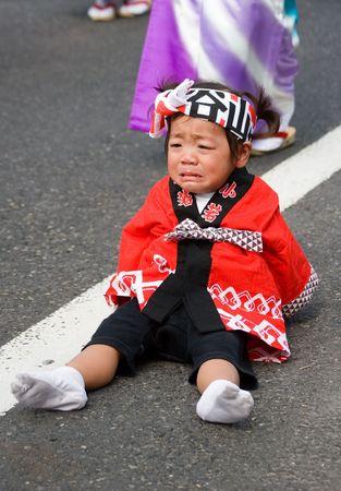 Kagoshima City, Japan, October 22, 2006. A tired young child dancer cries during the Taniyama Furusato Matsuri dance festival
