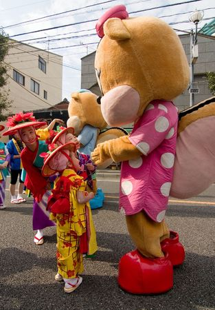 Kagoshima City, Japan, October 22, 2006. Young children in yukata kimono play with a mascot like character during the Taniyama Furusato Matsuri dance festival