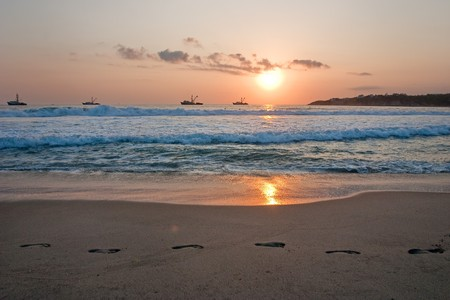 Beach sunset with ships and footprintsin the sand. photo