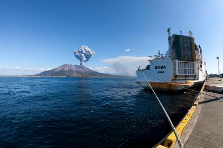 KAGOSHIMA CITY, JAPAN - FEBRUARY 15: Mt Sakurajima erupting with a ship in foreground. The volcano erupted over 800 times in 2010, Kagoshima City, Japan, February 15, 2011.