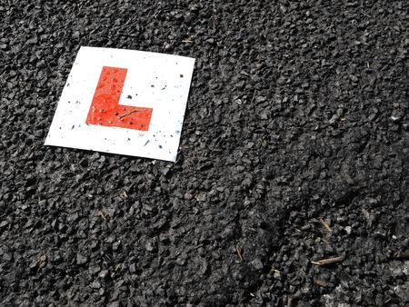 Learner drivers plate against black tarmac accident concept image
