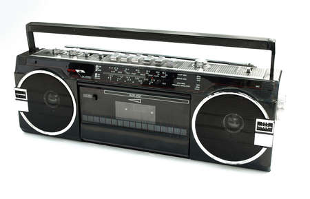 Dirty old 1980s style cassette player radio against a white background photo