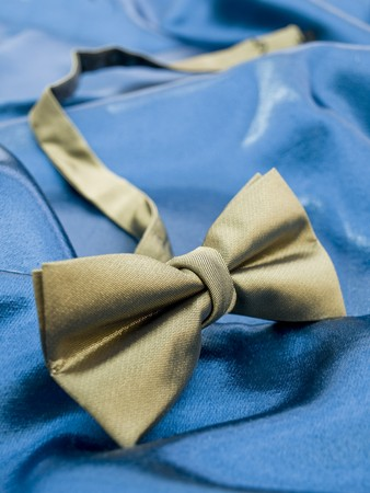 Gold bow tie against blue satin background. View my full portfolio for similar images. photo