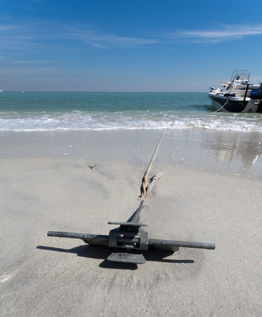 ship anchor: An anchor is positoned on the beach to secure the ship from getting away