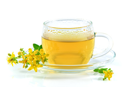 Tea with St. Johns wort in a glass cup isolated on a white background and the flowering herb hypericum