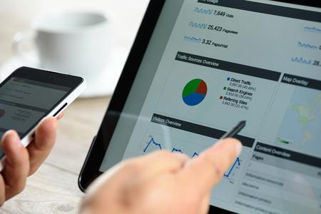 차트 및 커피와 전화 잔 태블릿 화면에 분석 데이터. 스톡 콘텐츠