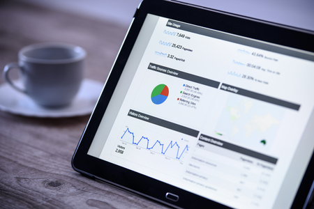 Charts and analytical data on the tablet screen with a cup of coffee on a wooden vintage table.