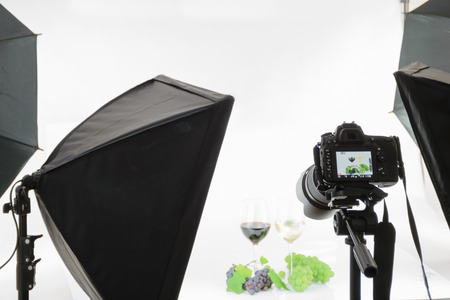 Professional SLR camera on a tripod takes a shot in the studio. Stock Photo