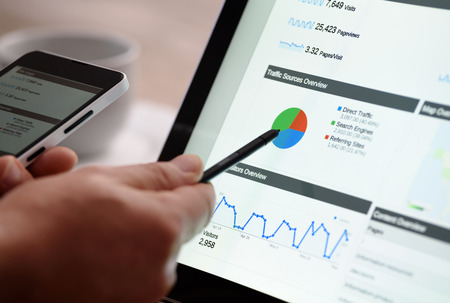 adwords: Business intelligence graphs on a tablet and a smartphone while working in the office