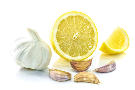 Garlic bulb and clove with sliced lemon isolated on a white background