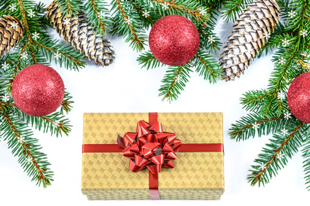 Overhead shot on branches of Siberian spruce and elegant cardboard box decorated with a red ribbon isolated on a white background Stock Photo