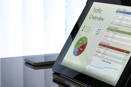사무실 창 옆에 스마트 폰이있는 태블릿 화면의 차트 및 데이터 스톡 콘텐츠