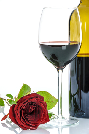 Beautiful red rose and wineglass of red wine and a bottle on a white background. Stock Photo