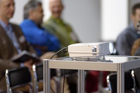 Witte multimediaprojector in een conferentieruimte met bluredmensen op de achtergrond Stockfoto