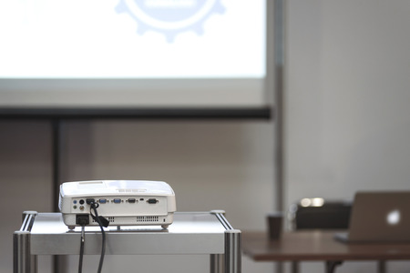 White multimedia projector in a conference room with blured projection screen and a lecturer desk on the background (reduced tone)