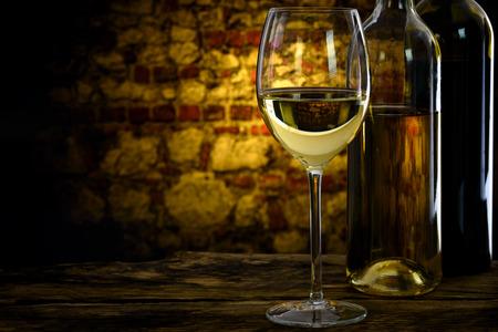 Crystal glass of white wine in the old vintage cellar ( low key)