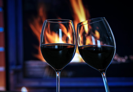Two glasses of red wine raised in a toast against a fire in the fireplace.