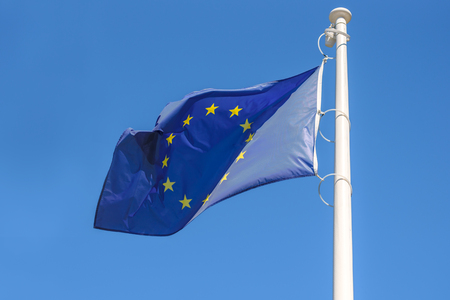 Flag of the European Union waving in the wind on a blue sky background