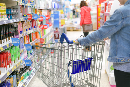 Nowy Sacz, Poland - March 29, 2017: Young woman pushing shopping cart through front of aisle with a variety of personal care products in a Tesco Hypermarket. Editorial
