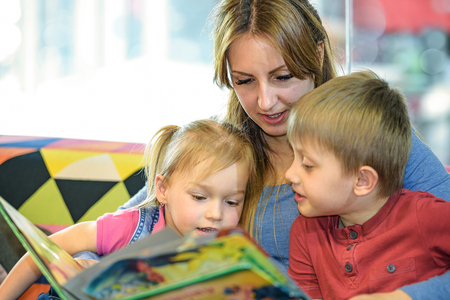 Portrait of pretty young women reading fairy tales with two children in the childrens playroom