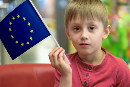 Little boy as a patriot holding in his hand a  paper flag of the European Union