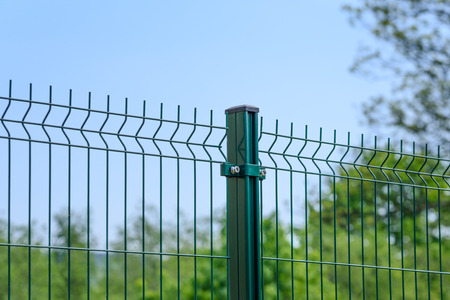 Close-up of a metal fence wire on blue sky background