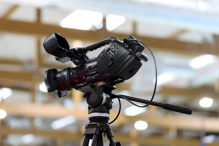 Generic professional video camera in studio on a tripod on a background of blurred lights. May depict third Party IP.