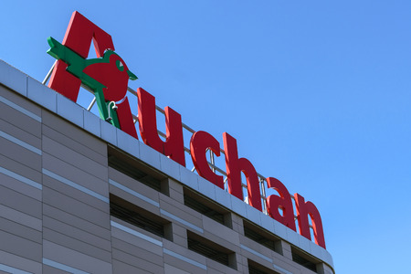 Krakow, Poland - 03 June 2017: Sign of the Auchan hypermarket on the blue sky in a sunny day. Auchan is a French international distribution hypermarket network.