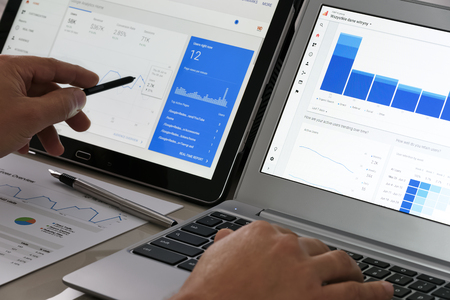 クルィニツァ ズドルイ, ポーランド-2017 年 7 月 11 日: ビジネスマンのオフィス彼のタブレットとノート パソコンのタッチ スクリーン上で Google Analyti 報道画像