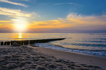 Sand on the beach and rippling sea on the background of the picturesque sky at sunset.