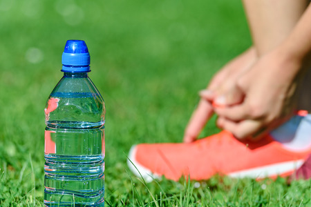 Break in training - mineral water on the grass and woman lacing shoes on the background Stock Photo