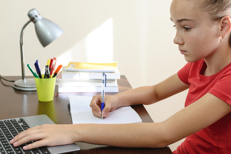 Young female student doing homework on a laptop in her room. Stock Photo