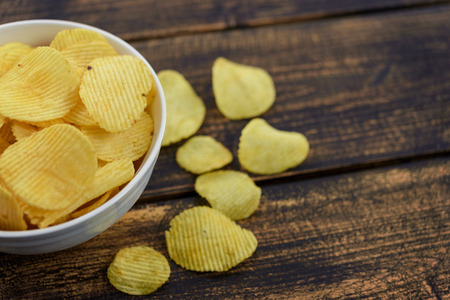 Crispy potato chips in a bowl on an old wooden vintage table. Stockfoto