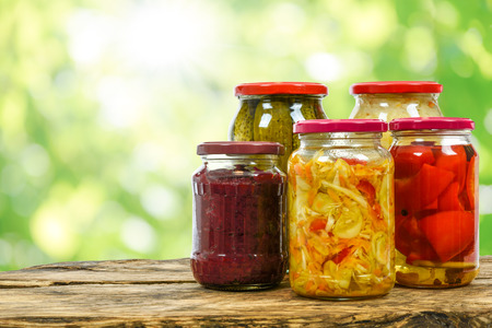 Composite image of jars with variety of homemade pickled vegetables on a wooden vintage table and on the blurred green garden background.